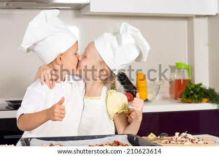 Cute Little Kid Chefs Kissing at Kitchen for the Success of Baking. - stock photo