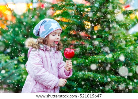 Cute little kid girl eating sugared apple on Christmas market. Happy child in winter fashion clothes with lights on background.