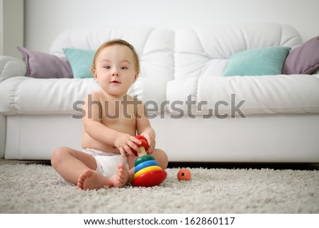 Cute little kid in diaper sits on carpet with pyramid at home.