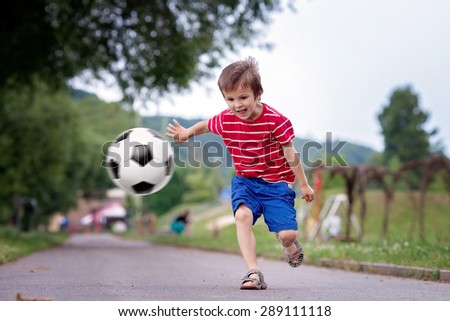 Cute little kid, playing football together, summertime. Children playing soccer outdoor