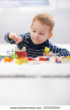Cute little kid playing on floor with building cubes at home. - stock photo