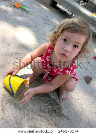 Cute little kid playing with yellow bucket and sand on the playground - stock photo