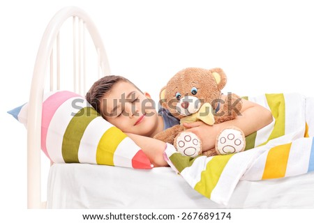 Cute little kid sleeping with a teddy bear covered with a blanket in bed isolated on white background - stock photo