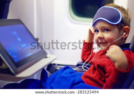 cute little kid watching cartoons during the long flight in airplane - stock photo