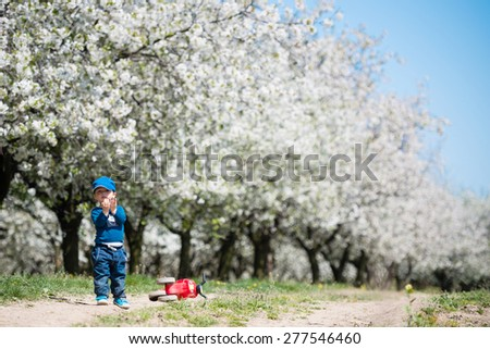 Cute little kid with beautiful blossoming cherry trees in background