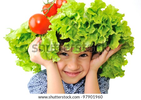 Cute little kid with tomato and salad hat on his head - stock photo