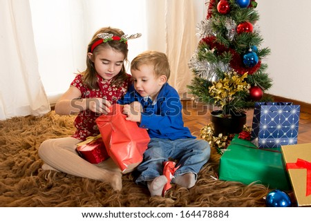 Cute little kids on rug opening Christmas Presents - stock photo