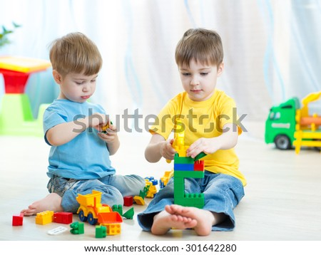 Cute little kids play with building bricks in preschool - stock photo