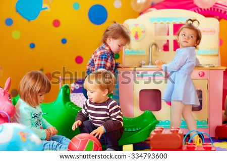 cute little kids playing with toys in nursery group of kindergarten - stock photo