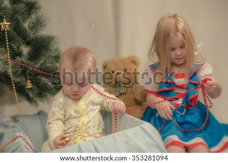 Cute little kids sit under the Christmas tree. Happy new year.