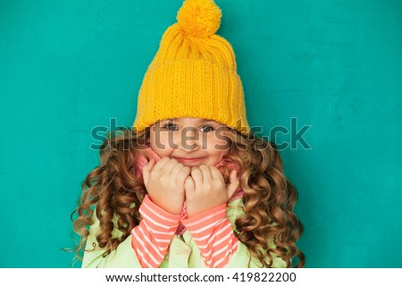 Cute little lady wearing yellow woolen cap and scarf against turquoise background - stock photo