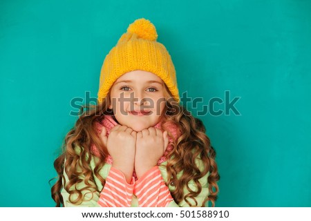 Cute little lady wearing yellow woolen cap and warm scarf against turquoise background