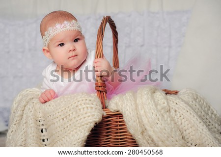Cute little 7 month baby girl in basket with lace headband and pink skirt