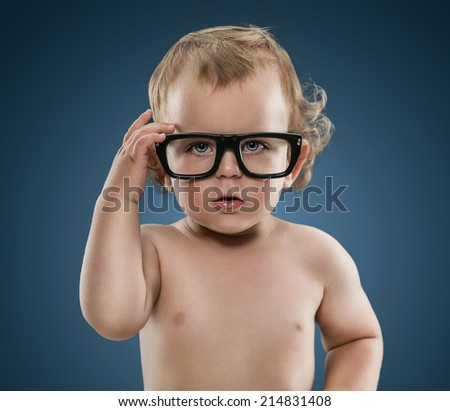 Cute little nerd boy wearing glasses isolated on blue background - stock photo