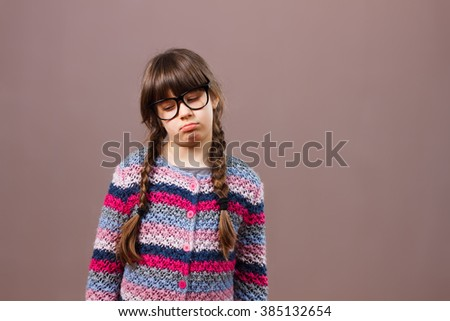 Cute little nerdy girl is very sad because of something.Sad little nerdy girl