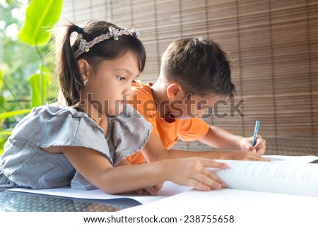 Cute ?little pan asian girl reading a story book sitting next to an older brother engrossed in coloring activity in home environment - stock photo