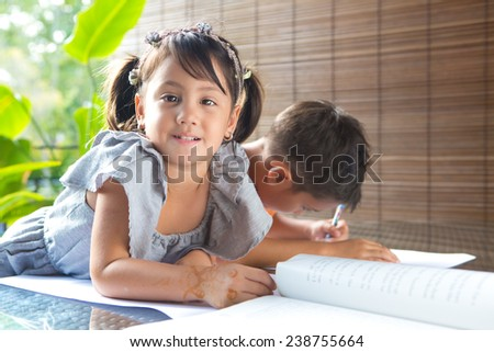 CuteÃ?Â??little pan asian girl smiling with a story book sitting next to an older brother engrossed in coloring activity in home environment - stock photo