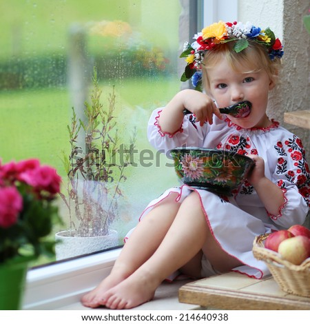 Cute little patriotic child, blonde curly toddler girl in traditional ukrainian dress and wreath sitting indoors next to a big window with garden view eating from painted wooden plate - stock photo