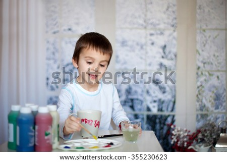 Cute little preschool boy, drawing picture on mug for his fathers birthday at home, wintertime