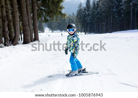 Cute little preschool child in blue jacket, skiing happily on a sunny day in Als