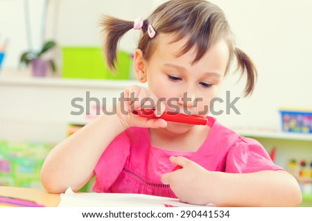 Cute little preschool girl drawing with colorful pencils - stock photo