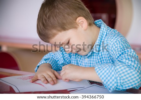 Cute little preschool kid boy in a blue plaid shirt drawing on the paper and smiling. Creative child at the table. Preschool art activities. Leisure with children. Young artist. - stock photo