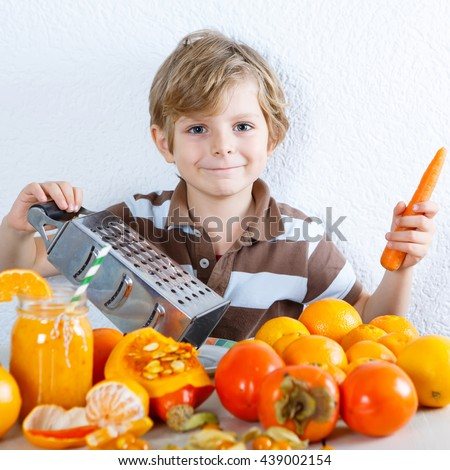 Cute little preschool kid boy making fresh healthy organic smoothie. Healthy meal and drink. Orange fruits and vegetables. - stock photo