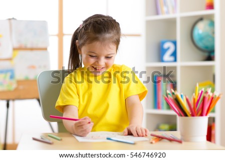 Cute little preschooler child girl drawing at home