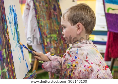 Cute little preschooler making a painting in art class - stock photo