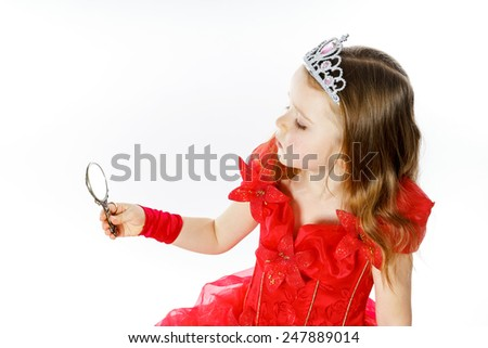Cute little princess dressed in red looking to the compact mirror isolated on white background - stock photo