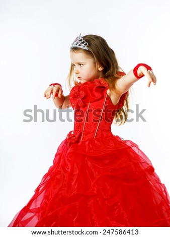 Cute little princess dressed in red  with crown on her head posing in studio. Children fashion.