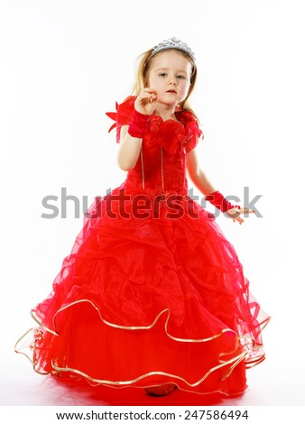 Cute little princess dressed in red  with crown on her head posing in studio. Children fashion. - stock photo