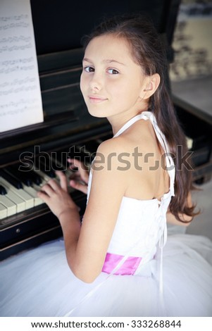 Cute little princess girl plays piano in the studio - stock photo
