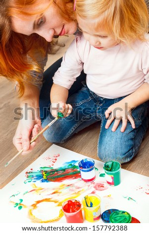 Cute little redhead girl painting with brush. - stock photo