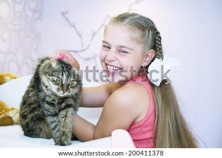 cute little school girl hugging her cat close up portrait - stock photo