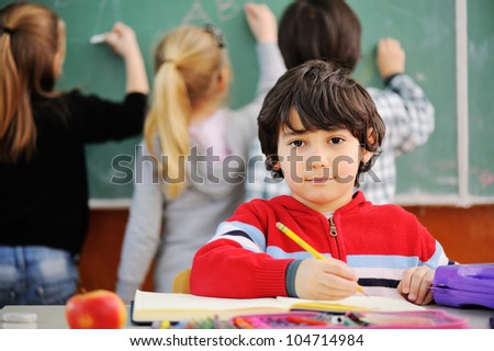 Cute little schoolboy drawing an apple and looking at camera - stock photo