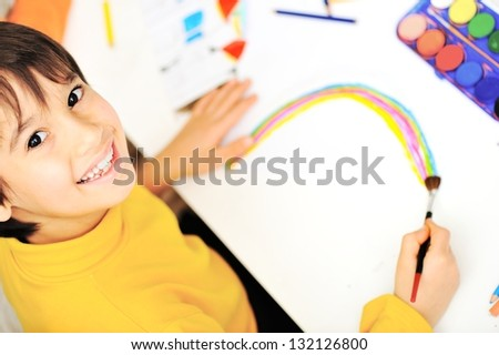 Cute little schoolboy drawing an house and looking at camera - stock photo