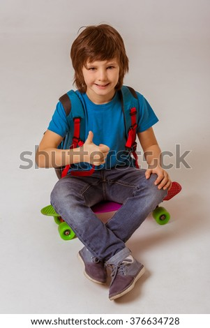 Cute little schoolboy in a blue t-shirt with a backpack showing OK sign, looking in camera and smiling while sitting on a skateboard on a gray background - stock photo