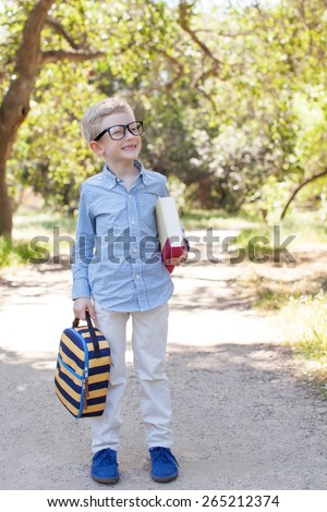 cute little schoolboy in glasses holding book and lunchbag ready to go to school, back to school concept - stock photo