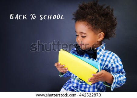 Cute little schoolboy portrait, adorable african child with books in hands over dark background, back to school concept - stock photo