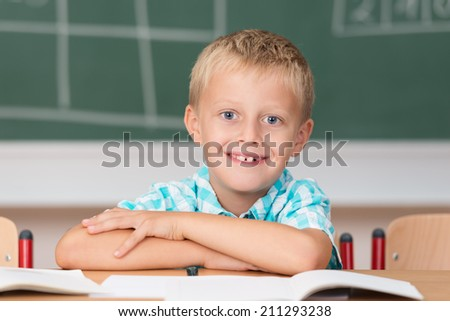 Cute little schoolboy with a happy grin sitting at his desk in front of the blackboard with his arms folded on his school books - stock photo