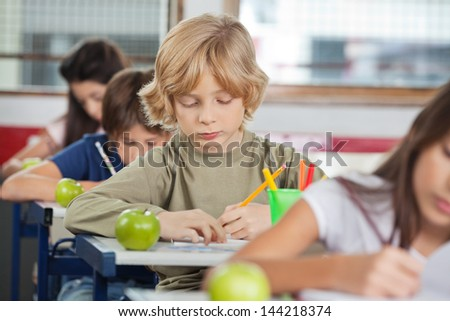 Cute little schoolboy writing while sitting at desk with classmates in a row