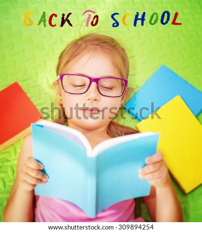 Cute little schoolgirl doing homework, lying down on the floor at home and reading book, text on the floor : back to school - stock photo