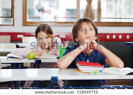 Cute little schoolgirl looking at schoolboy while sitting in classroom - stock photo
