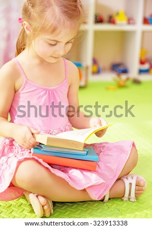 Cute little schoolgirl sitting at home on the floor with books and preparing to go to first class, doing homework, back to school - stock photo