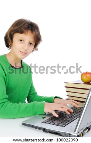 Cute little schoolgirl with laptop and bunch of books in front of her - stock photo