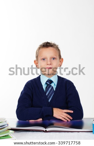 Cute little serious boy is looking at pictures in a book, isolated over white background
