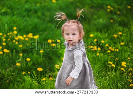 Cute little serious thoughtful girl looking for someone or something on the meadow with dandelions - stock photo