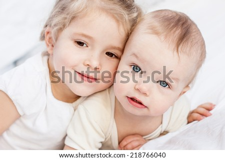 cute little sister hugging her brother on a white background ( focus on one child ) - stock photo