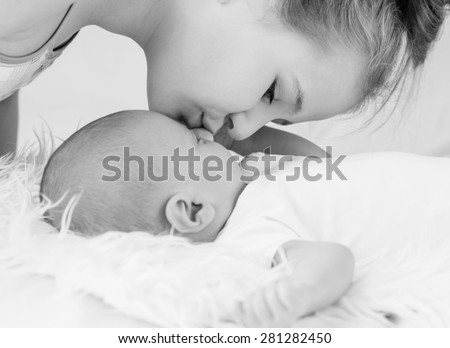 Cute little sister kisses newborn brother ( black and white ) - stock photo